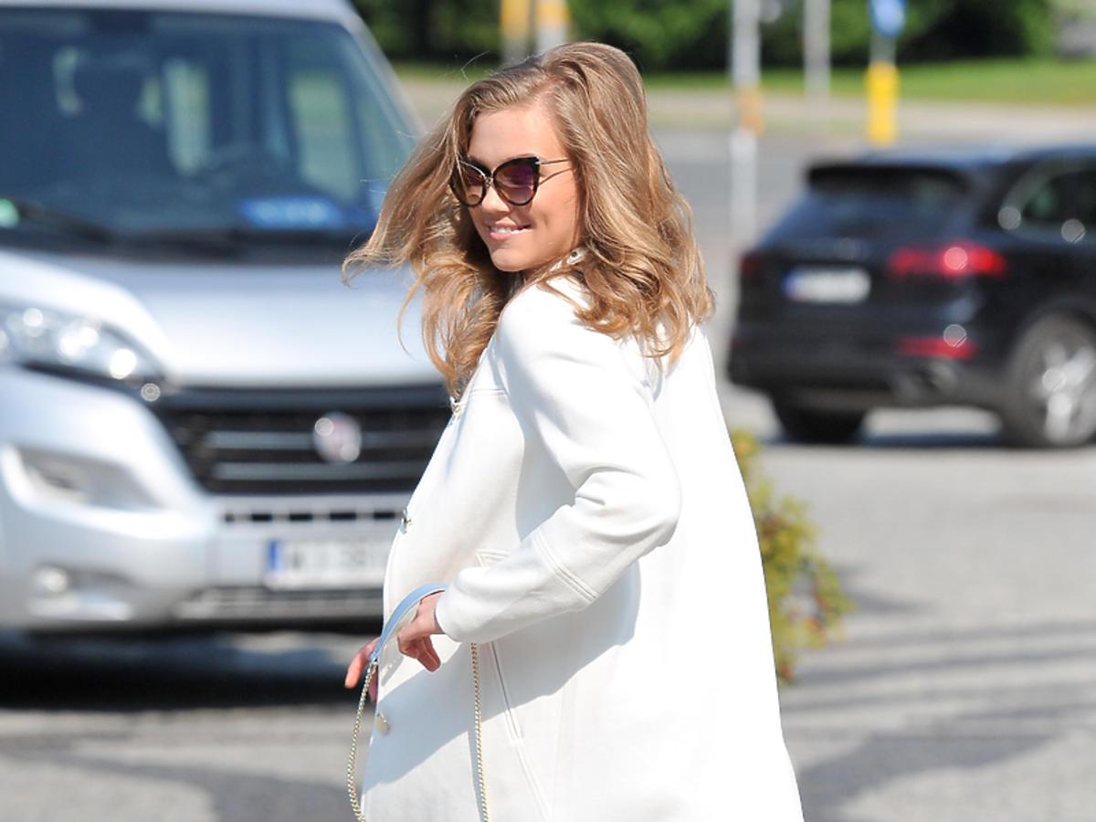Agnieszka Kaczorowska w białym płaszczu i szerokich spodniach