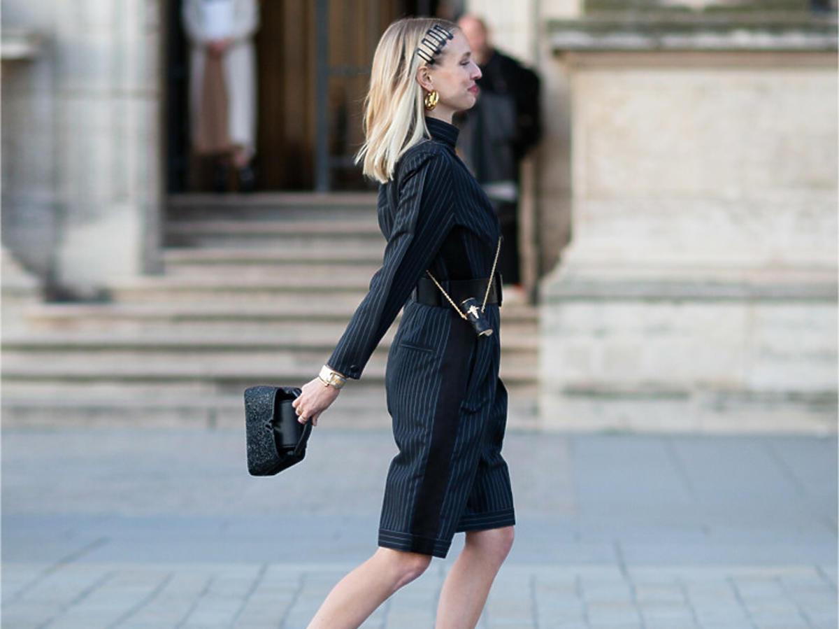 Blondynka w czarnej stylizacji i czarnych botkach na słupku