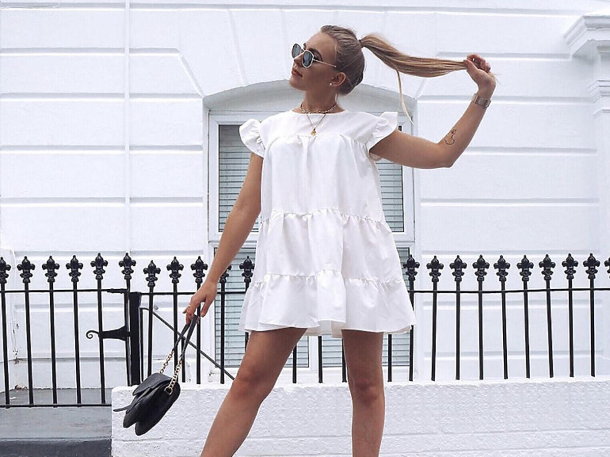 """Influencerka w białej sukience i czarnych botkach na słupku ze """"skarpetą"""""""