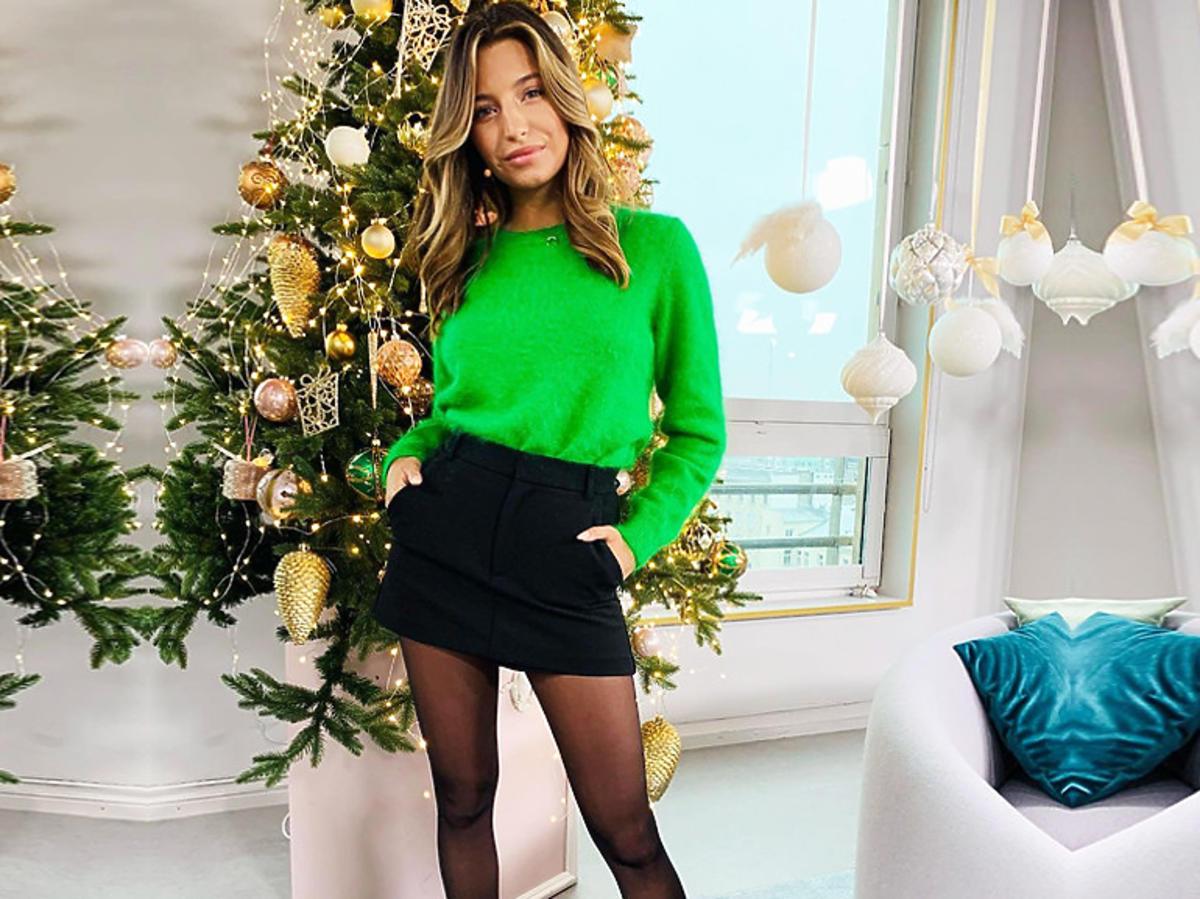 Julia Wieniawa w zielonym sweterku, czarnych szortach i czarnych botkach
