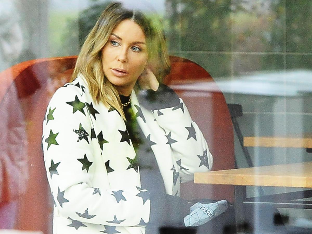 Małgorzata Rozenek-Majdan w białym płaszczu w czarne gwiazdki i czarnych botkach