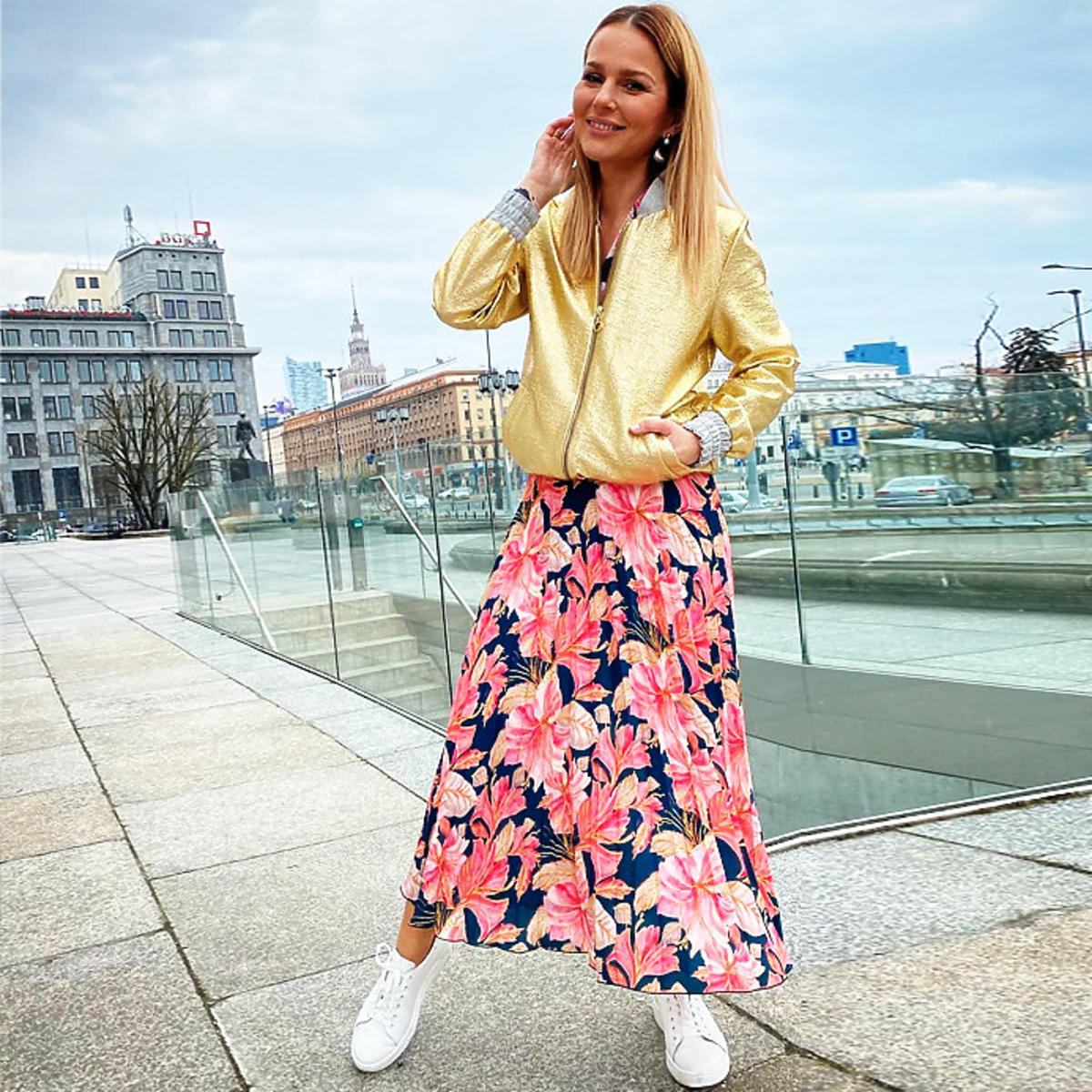 Paulina Sykut w białych adidasach, kwiecistej spódnicy i złotej kurtce