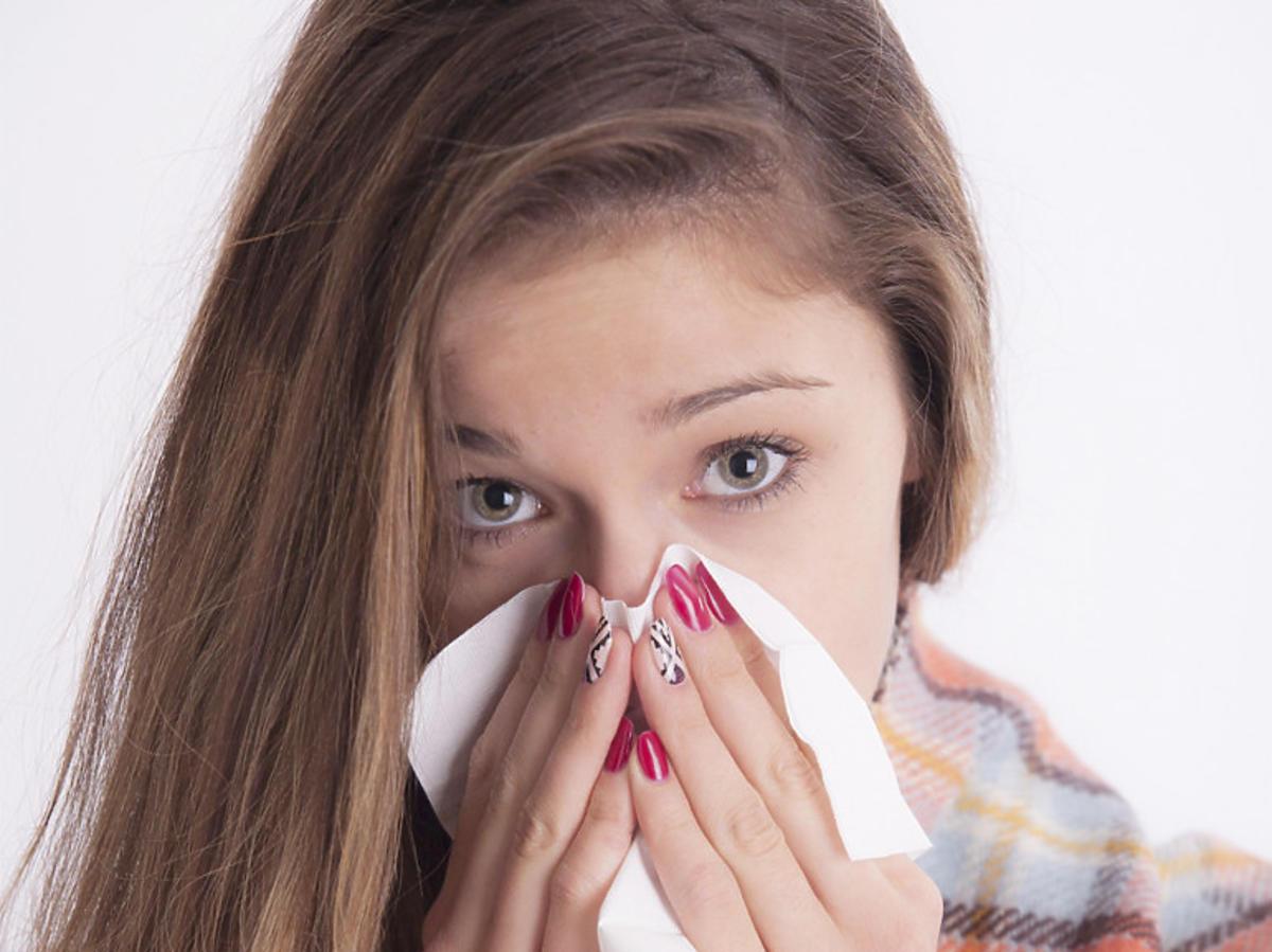 Przeziębiona kobieta z chusteczką