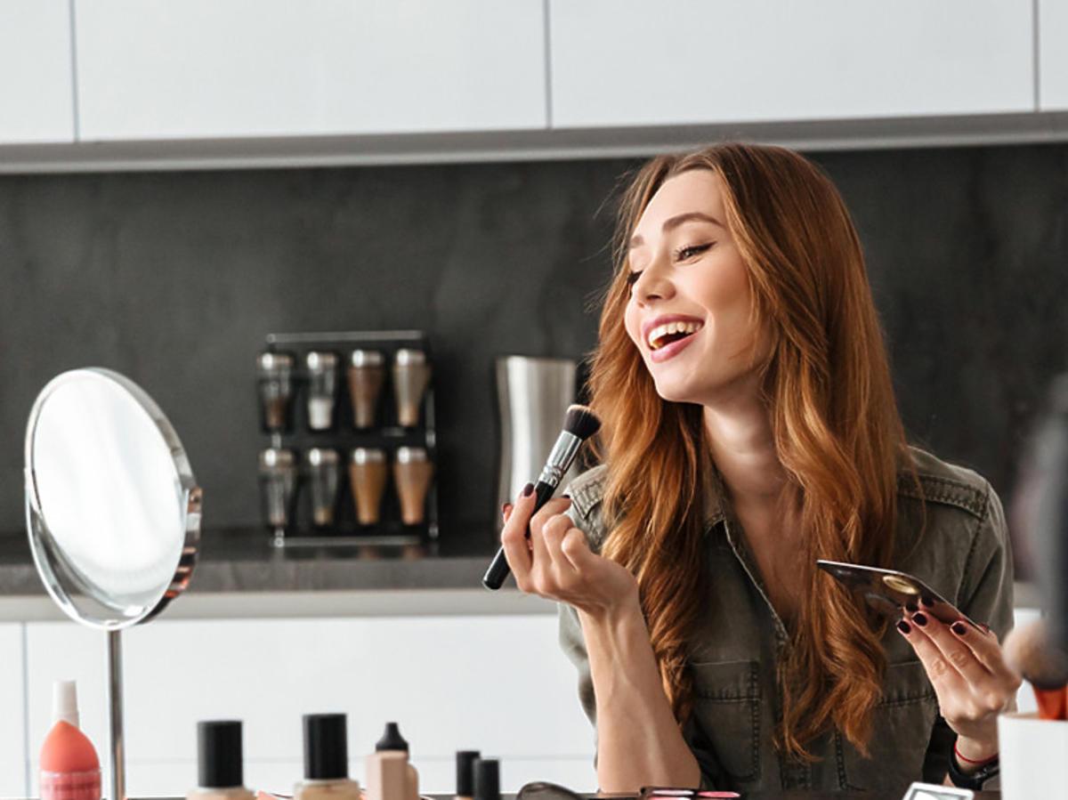 Kobieta malująca się przed lustrem