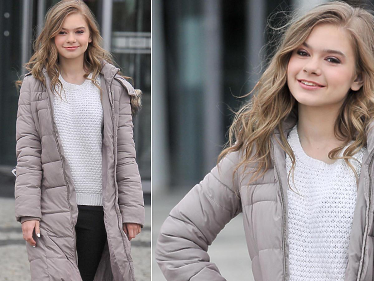Julia Wróblewska w białym swetrze i kurtce zimowej wychodzi z TVP