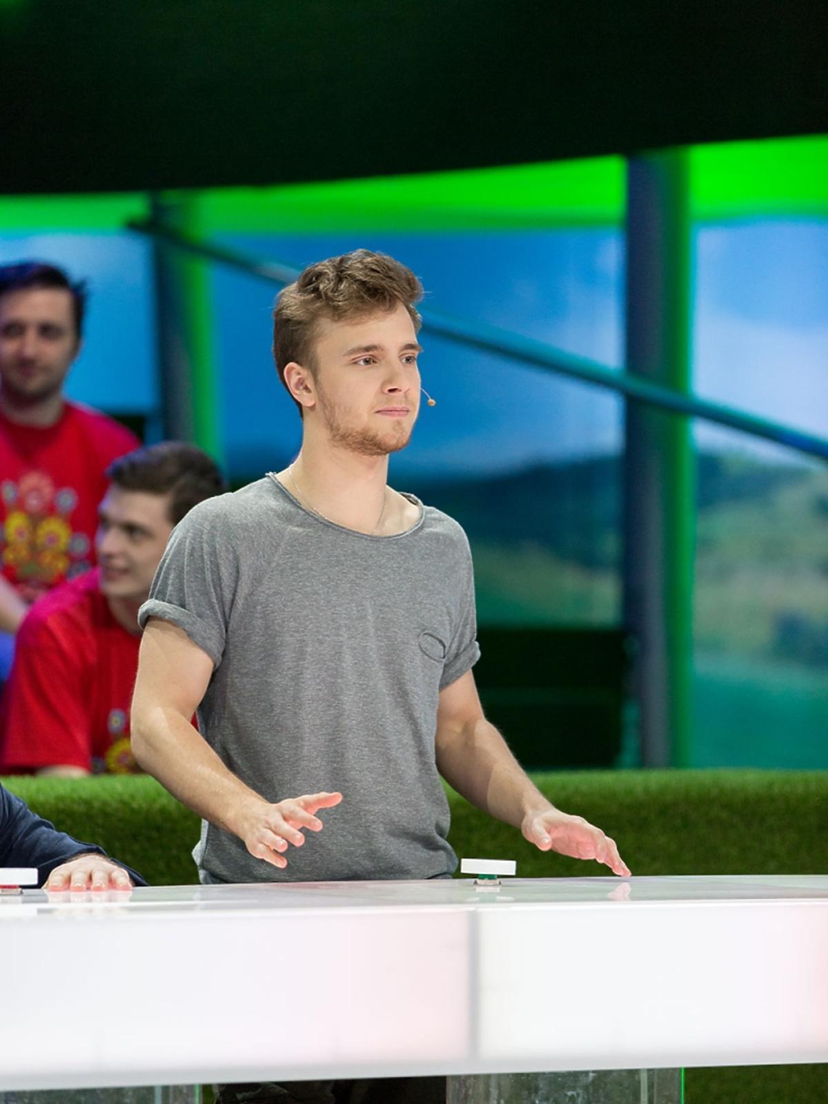 Maciej Musiał w szarym T-shircie w TVP