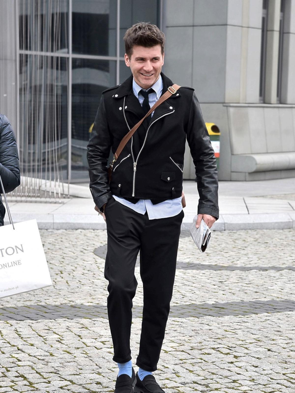 Tomasz Kammel w czarnej kurtce i niebieskich skarpetkach